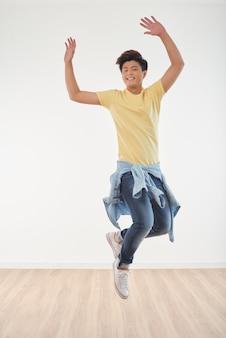 Longitud total de alegre chico asiático bailando