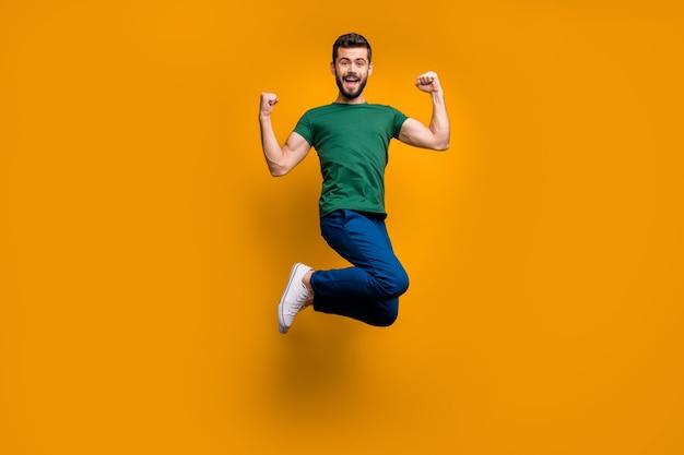 Longitud total alegre chico cobarde saltar levantar puños gritar sí
