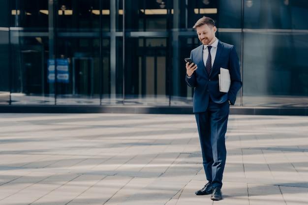Longitud total de alegre empleado de la firma masculina en traje azul con mensajes de texto de periódico o chateando en el teléfono inteligente mientras está de pie junto al edificio de vidrio al aire libre, gente de negocios y concepto de tecnologías