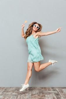 Longitud total de alegre hermosa joven en gafas de sol saltando por encima de la pared gris