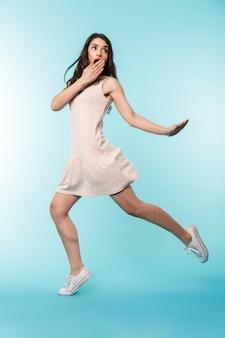 Longitud total de una alegre joven morena saltando sobre fondo azul