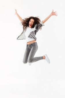 Longitud total alegre mujer rizada saltando y mirando a otro lado sobre la pared blanca