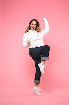 Longitud total alegre mujer rubia gritando vistiendo ropa casual se regocija y mirando al frente sobre rosa bwall