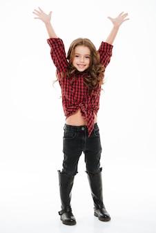 Longitud total de alegre niña de pie con las manos levantadas