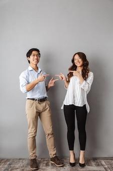 Longitud total de la alegre pareja asiática de pie, señalando con el dedo el uno al otro