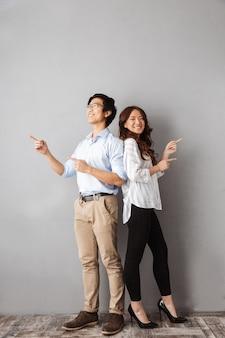 Longitud total de la alegre pareja asiática de pie, señalando con el dedo a los lados