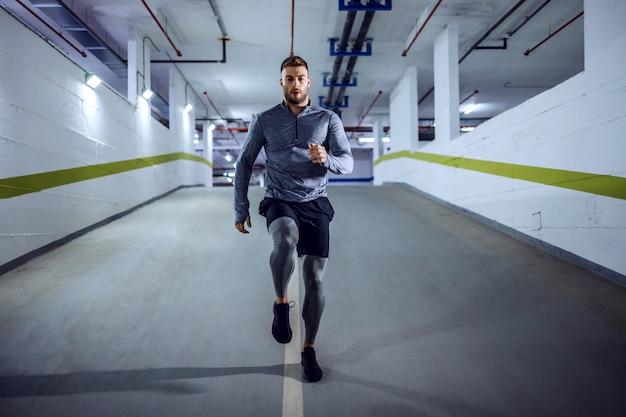 Longitud total de apuesto deportista caucásico musculoso en ropa activa en garaje subterráneo por la noche. concepto de vida urbana.