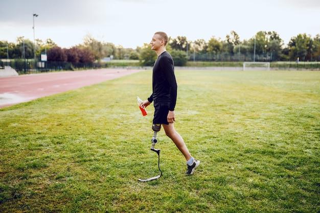 Longitud total de apuesto hombre deportivo caucásico discapacitado en ropa deportiva y con pierna artificial caminando en la cancha de fútbol y sosteniendo un refresco.