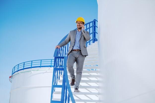 Longitud total de apuesto hombre de negocios caucásico en traje y casco en la cabeza bajando las escaleras en el tanque de almacenamiento de combustible y hablando por teléfono.