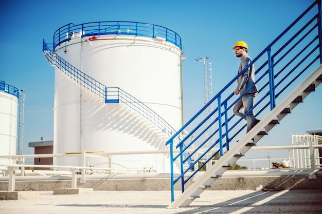 Longitud total de apuesto hombre de negocios del cáucaso en traje y casco en la cabeza bajando las escaleras en el tanque de almacenamiento de petróleo.