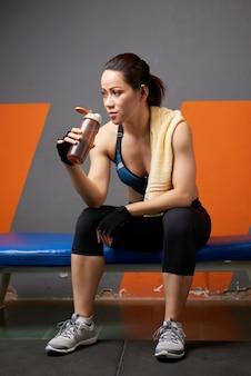 Longitud total del atleta bebiendo agua de la botella de gimnasia agotada después del entrenamiento