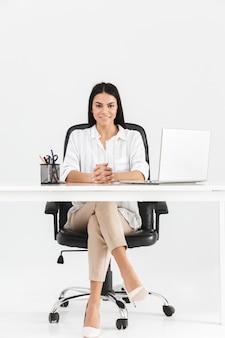 Longitud total de una atractiva joven empresaria segura sentada en el escritorio aislado sobre la pared blanca