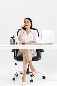Longitud total de una atractiva joven empresaria sentada en el escritorio aislado sobre una pared blanca, hablando por teléfono móvil