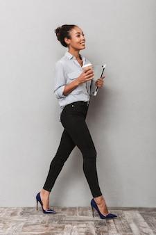 Longitud total de una atractiva joven mujer de negocios africana con camisa caminando aislado, sosteniendo el portátil, bebiendo café para llevar