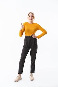 Longitud total de una atractiva joven rubia sonriente vistiendo suéter que se encuentran aisladas sobre la pared blanca, pulgares arriba