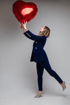 Longitud total de atractiva mujer caucásica en traje de terciopelo azul con chaqueta y pantalón y tacones altos y brillantes sosteniendo el símbolo rojo en forma de corazón del globo del amor