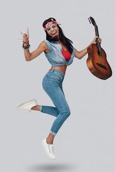 Longitud total de atractiva mujer joven con estilo que lleva la guitarra acústica y sonriendo mientras flota contra el fondo gris