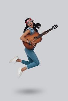 Longitud total de atractiva mujer joven con estilo tocando la guitarra acústica y sonriendo mientras flota contra el fondo gris