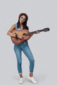 Longitud total de atractiva mujer joven con estilo tocando la guitarra acústica y sonriendo mientras está de pie contra el fondo gris