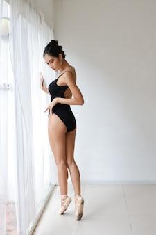 Longitud total aturdimiento de encantadora mujer asiática en traje negro haciendo ballet bailando en estudio de pared blanca