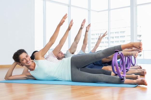 Longitud total de la clase de aptitud que estira las piernas y las manos en fila en la clase de yoga
