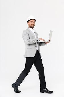 Longitud total de un constructor de hombre barbudo confiado vistiendo traje y casco que se encuentran aisladas sobre una pared blanca, usando una computadora portátil