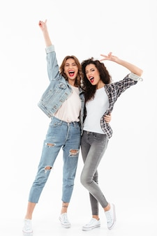 Longitud total dos alegres chicas de pie juntas y mostrando gestos de paz sobre la pared blanca