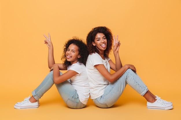 Longitud total de dos hermanas africanas sentadas espalda con espalda