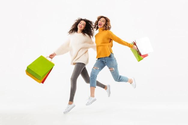 Longitud total dos muchachas alegres en suéteres corriendo juntas con paquetes y mirando a otro lado sobre la pared blanca