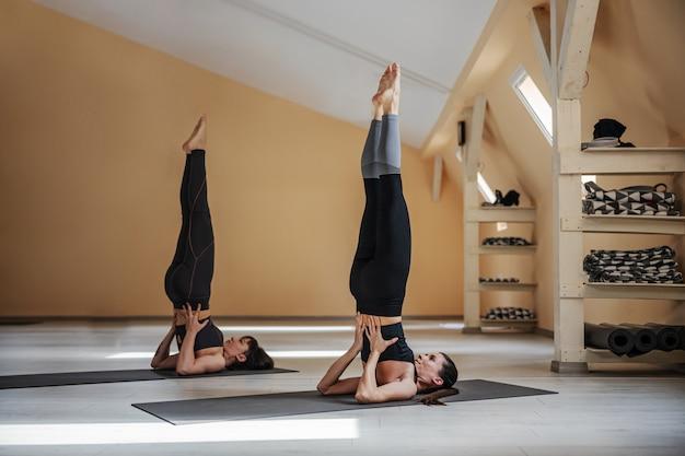 Longitud total de dos mujeres jóvenes en pose de yoga de soporte de hombro apoyado.