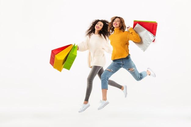 Longitud total dos niñas felices en suéteres corriendo juntos con paquetes y mirando a otro lado sobre la pared blanca