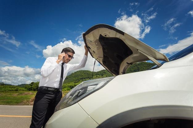 Longitud total de empresario preocupado por coche averiado en el campo. Foto Premium