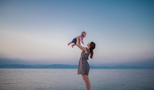 Longitud total de la encantadora morena levantando a su adorable hijo mientras está de pie en la playa.