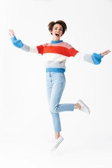 Longitud total de feliz alegre niña vistiendo suéter saltando aislado en blanco