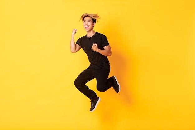 Longitud total de feliz atractivo chico asiático en ropa negra saltando y celebrando la victoria, lograr el objetivo, de pie pared amarilla, triunfando.