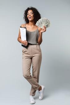 Longitud total de una feliz joven africana vestida casualmente de pie aislado, sosteniendo un bloc de notas, mostrando billetes de dinero
