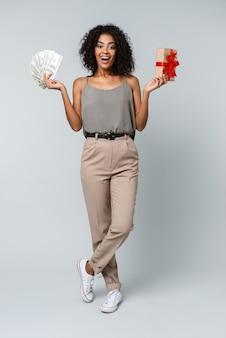 Longitud total de una feliz joven africana vestida casualmente de pie aislado, sosteniendo una caja de regalo, mostrando billetes de dinero