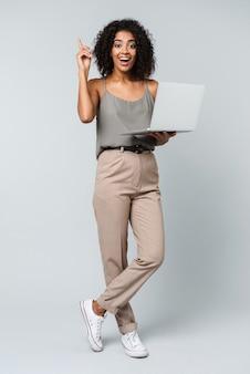 Longitud total de una feliz joven africana vestida casualmente de pie aislado, trabajando en equipo portátil, teniendo una idea