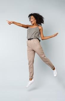 Longitud total de una feliz joven africana vestida casualmente saltando aislado, apuntando al espacio de la copia