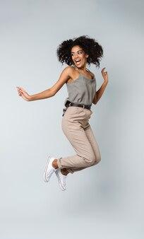 Longitud total de una feliz joven africana vestida casualmente saltando aislado