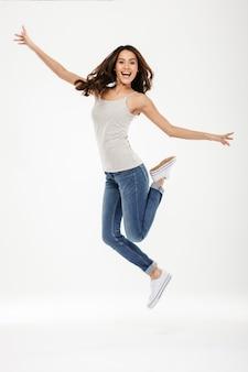 Longitud total feliz mujer morena saltando y se regocija mientras mira a la cámara sobre gris