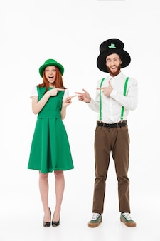 Longitud total de una feliz pareja joven con disfraces, celebrando el día de san patricio aislado sobre una pared blanca, apuntando con el dedo el uno al otro