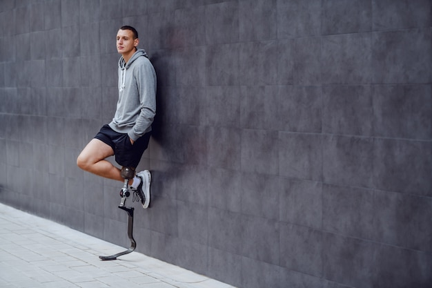 Longitud total de guapo deportista caucásico con pierna artificial apoyado en la pared exterior y con las manos en los bolsillos.