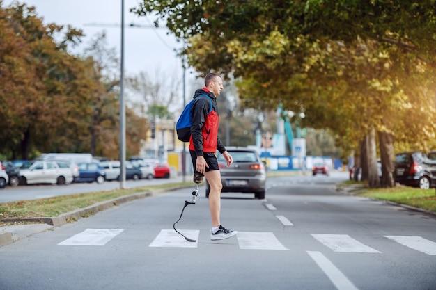Longitud total de guapo deportista discapacitado caucásico en ropa deportiva, con pierna artificial y mochila cruzando la calle.
