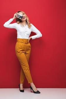Longitud total de una hermosa joven rubia de pie sobre fondo rojo, sosteniendo la cámara de fotos