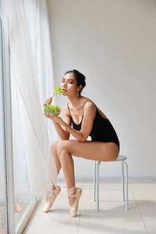 Longitud total hermosa mujer asiática joven sana comiendo ensalada después de entrenar ballet mientras está sentado