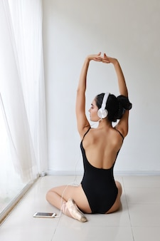 Longitud total hermosa mujer joven asiática saludable y deportiva en ropa deportiva negra con auriculares, escuchando música desde el teléfono móvil mientras se entrena bailando ballet
