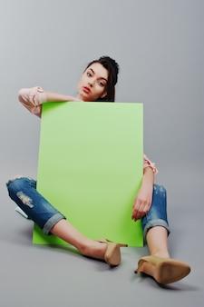 Longitud total de hermosa niña sentada, sosteniendo la pancarta publicitaria en blanco verde, sobre fondo gris
