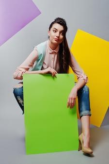 Longitud total de hermosa niña sentada, sosteniendo el tablero publicitario en blanco verde, sobre fondo gris y pancarta amarilla y violeta