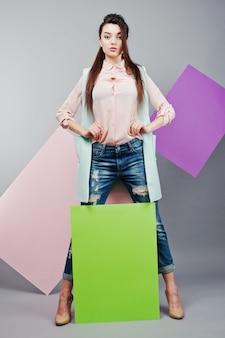 Longitud total de hermosa niña, con tablero publicitario en blanco verde, sobre fondo gris y pancarta rosa y violeta